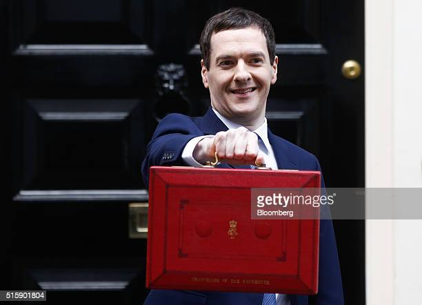 George Osborne UK chancellor of the exchequer holds the dispatch box containing the budget as he exits 11 Downing Street in London UK on Wednesday...