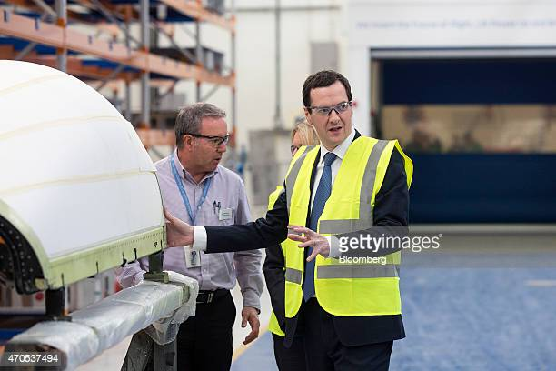 George Osborne UK chancellor of the exchequer looks at a composite piece for an aircraft as he tours the General Electric Co aviation center while...