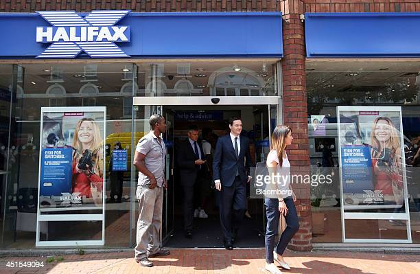 George Osborne UK chancellor of the exchequer second right exits a Halifax bank branch a unit of Lloyds Banking Group Plc in London UK on Tuesday...