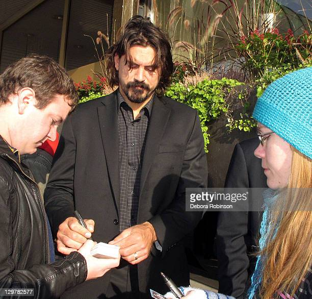 George Parros of the Anaheim Ducks autographs memorabilia for fans before heading into the arena before the game against the New York Rangers October...