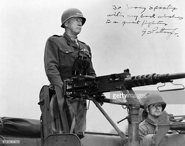 George Patton , American general, stands on a military vehicle in front of an artillery gun.