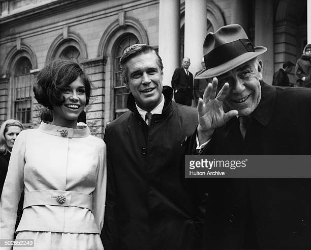 """George Peppard and Mary Tyler Moore stand on the street in a scene of the movie """"What's So Bad About Feeling Good?"""" circa 1968."""