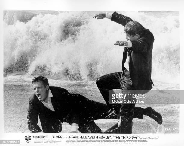 """George Peppard is attacked by Arte Johnson in the surf in a scene from the Warner Bros. Movie """"The Third Day"""", circa 1965."""