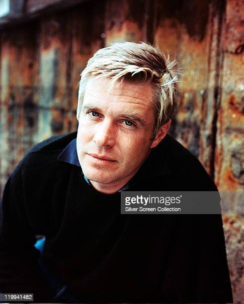 George Peppard US actor wearing a black jumper as he poses against a rusted surface circa 1960