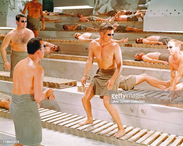 George Peppard US actor with a towel wrapped around his waist and wearing a pair of solarium goggles as he nervously looks at three approaching men...