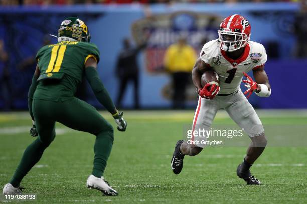 George Pickens of the Georgia Bulldogs avoids a tackle by Jameson Houston of the Baylor Bears during the Allstate Sugar Bowl at Mercedes Benz...