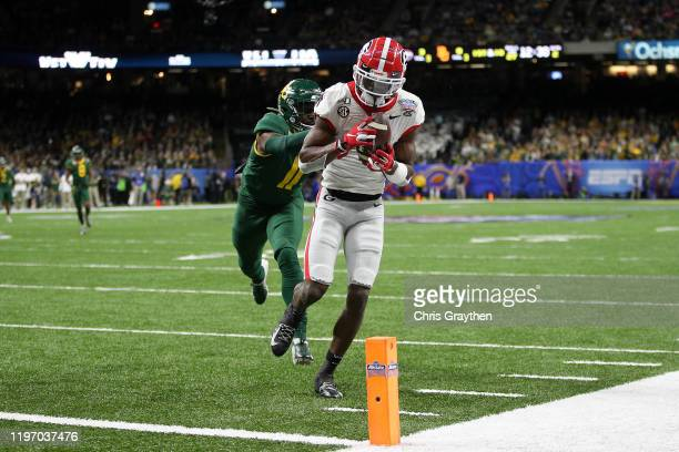 George Pickens of the Georgia Bulldogs catches a touchdown pass over Jameson Houston of the Baylor Bears during the Allstate Sugar Bowl at Mercedes...