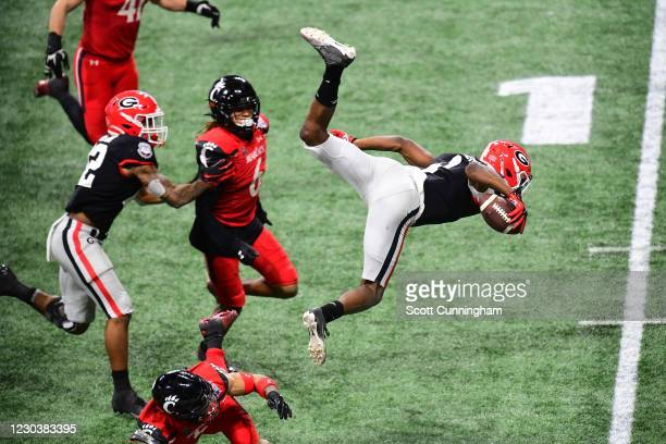 George Pickens of the Georgia Bulldogs is upended by Darrick Forrest of the Cincinnati Bearcats during Chick-fil-A Peach Bowl at Mercedes-Benz...