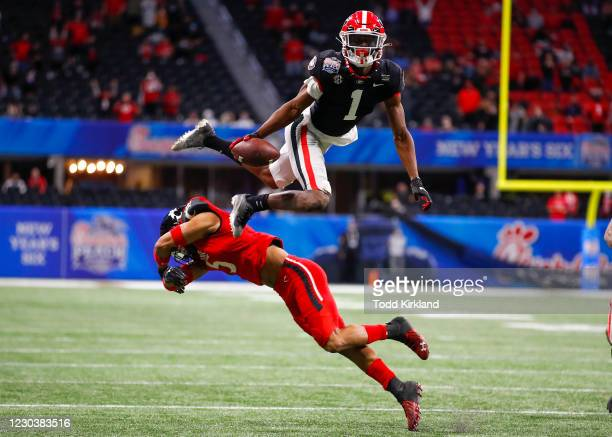 George Pickens of the Georgia Bulldogs leaps over the top of Darrick Forrest of the Cincinnati Bearcats during the second half of the Chick-fil-A...
