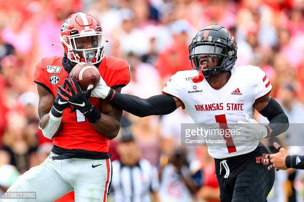 George Pickens of the Georgia Bulldogs reaches for a pass under tight coverage from Jerry Jacobs of the Arkansas State Red Wolves during the first...