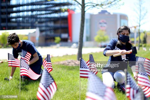 George Potenza and Faleehah Dam both of Foxborough plant flags outside of Gillette Stadium on May 21 2020 in Foxborough Massachusetts The Patriots...