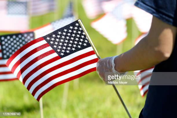 George Potenza of Foxborough wears gloves as he plants a flag outside of Gillette Stadium on May 21 2020 in Foxborough Massachusetts The Patriots...