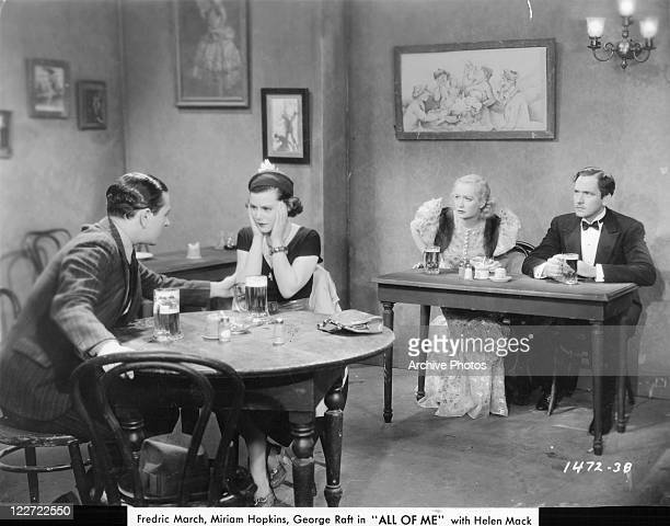 George Raft and Helen Mack sitting at a separate table than Miriam Hopkins and Fredric March in a scene from the film 'All Of Me' 1934