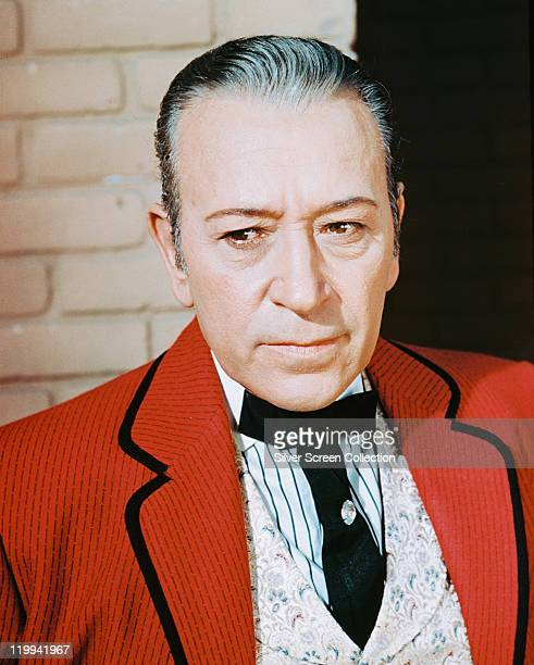 George Raft US actor wearing a red jacket with black trim and a black tie in a publicity portrait issued for the film 'Around the World in 80 Days'...