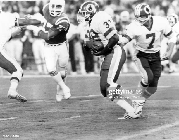 George Rogers, football player for the Washington Redskins, has the ball during a football game against the New England Patriots, Washington, DC,...
