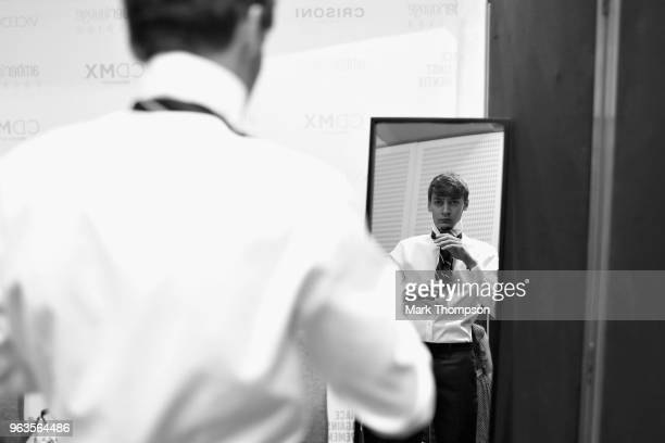 George Russell of Great Britain and Mercedes prepares backstage at the Amber Lounge Fashion show during previews ahead of the Monaco Formula One...