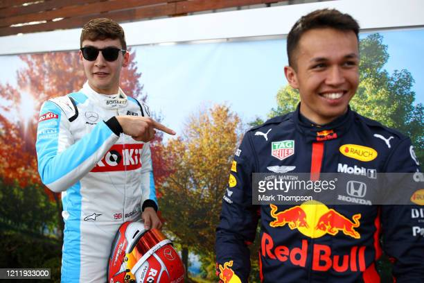 George Russell of Great Britain and Williams and Alexander Albon of Thailand and Red Bull Racing share a joke in the paddock during previews ahead of...