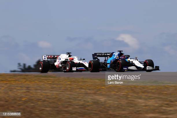 George Russell of Great Britain driving the Williams Racing FW43B Mercedes and Nikita Mazepin of Russia driving the Haas F1 Team VF-21 Ferrari on...