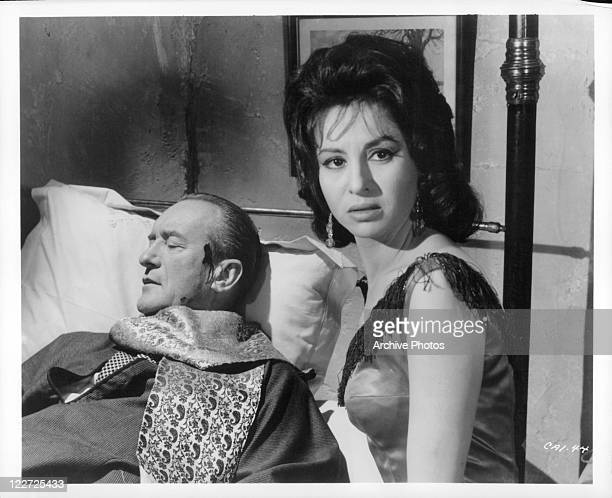 George Sanders seeks help at the house of dancing girl Faten Hamama after being wounded in a scene from the film 'Cairo' 1963