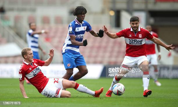George Saville and Sam Morsy of Middlesbrough battle for the ball with Ovie Ejaria of Reading FC during the Sky Bet Championship match between...