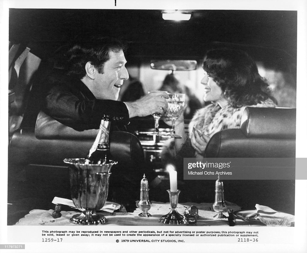 George Segal and Natalie Wood celebrate his birthday in the family car in a scene from the film 'The Last Married Couple in America', 1980.