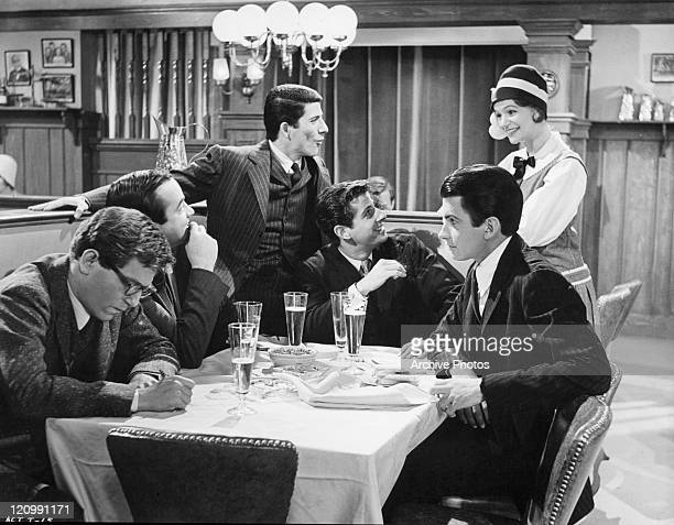 George Segal, David Doyle, Bert Convy, Jonathan Goldsmith, and George Hamilton sit around the table with drinks in a scene from the film 'Act One',...