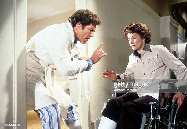 George Segal standing with a cast on his leg as Glenda Jackson sits in a wheelchair in a scene from the film 'Lost And Found' 1979