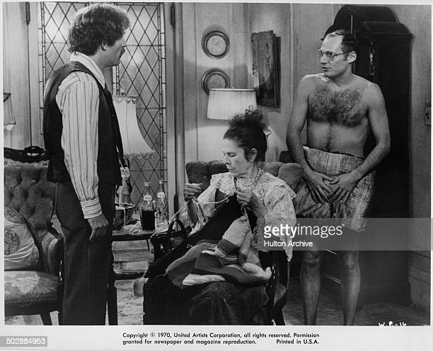George Segal talks to Ron Leibman as Ruth Gordon knits in a chair in a scene from the United Artist movie Where's Poppa circa 1970