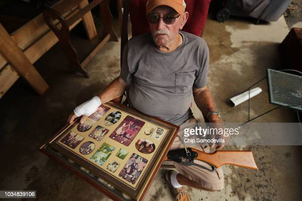George Skinner holds family photographs and an air rifle in his lap as friends and family help salvage belongings from his home, damaged by...