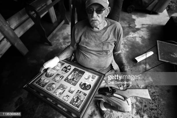 George Skinner holds family photographs and an air rifle in his lap as friends and family help salvage belongings from his home which was damaged by...