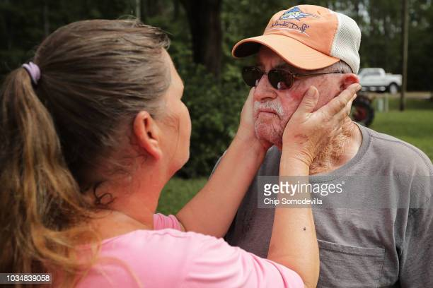 George Skinner is comforted by neighbor Mary Ann Dunn after both of their homes were damaged by floodwaters from the Nuese River during Hurricane...