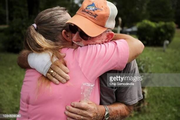 George Skinner is embraced by neighbor Mary Ann Dunn after both of their homes were damaged by floodwaters from the Nuese River during Hurricane...