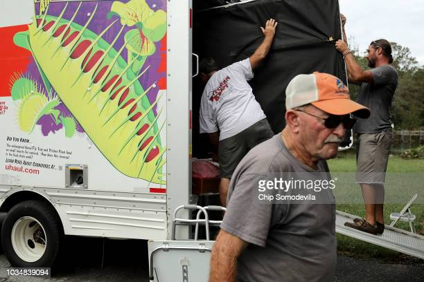 George Skinner supervises as family and friends help salvage belongings from his home, damaged by floodwaters from the Nuese River during Hurricane...