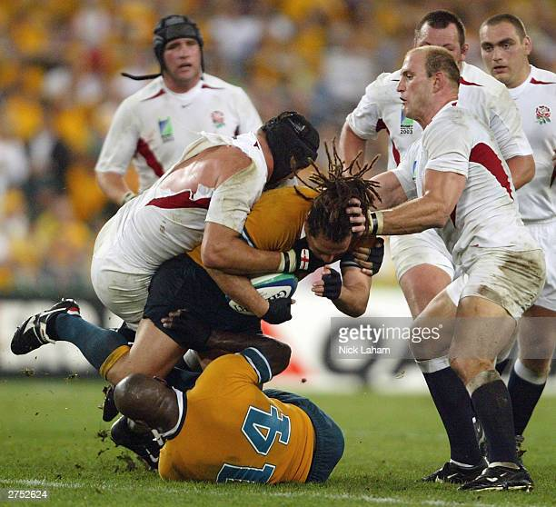 George Smith of Australia is tackled by Ben Kay and Lawrence Dallaglio of England during the Rugby World Cup Final match between Australia and...