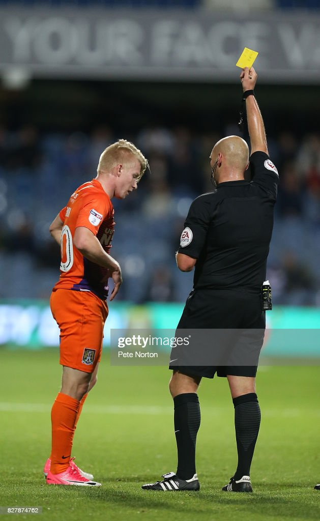 George Smith of Northampton Town is shown a yellow card by referee Charles Breakspear during the Carabao Cup first round match between Queens Park Rangers and Northampton Town at Loftus Road on August 8, 2017 in London, England.