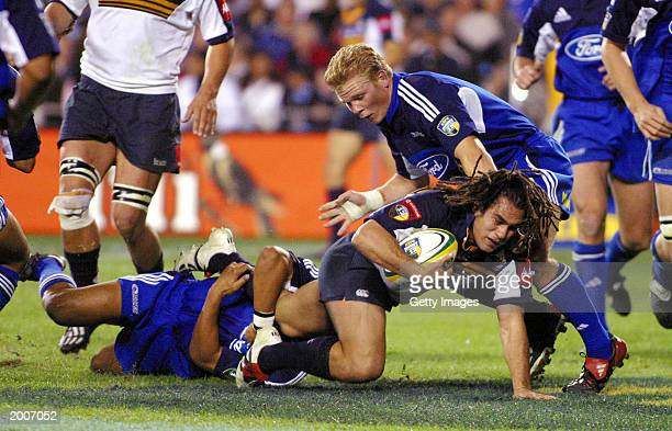George Smith of the Brumbies is tackled by Joe Rokocoko and Daniel Braid of the Blues during the Super 12 match between the Brumbies and the Blues...