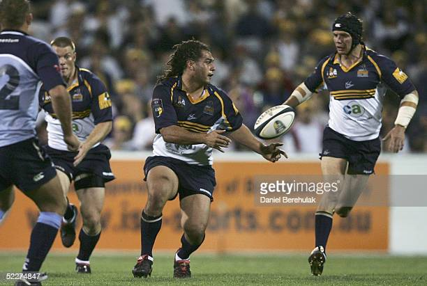 George Smith of the Brumbies off loads to Stephen Larkham during the Tooheys New Super 12 Rugby Union match between the Brumbies and the Bulls at...