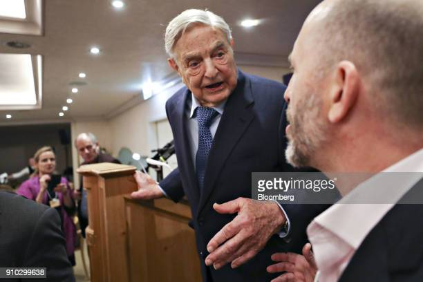 George Soros billionaire and founder of Soros Fund Management LLC speaks to an attendee on day three of the World Economic Forum in Davos Switzerland...