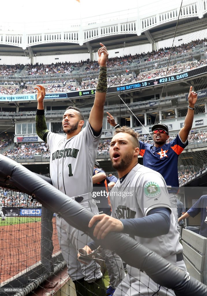 George Springer #4 and Carlos Correa #1 of the Houston Astros celebrate teammate J.D. Davis's three run home run in the second inning against the New York Yankees at Yankee Stadium on May 28, 2018 in the Bronx borough of New York City.MLB players across the league are wearing special uniforms to commemorate Memorial Day.