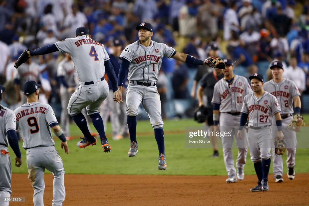 George Springer #4 and Carlos Correa #1 of the Houston Astros celebrate after defeating the Los Angeles Dodgers 7-6 in eleven innings to win game two of the 2017 World Series at Dodger Stadium on October 25, 2017 in Los Angeles, California.