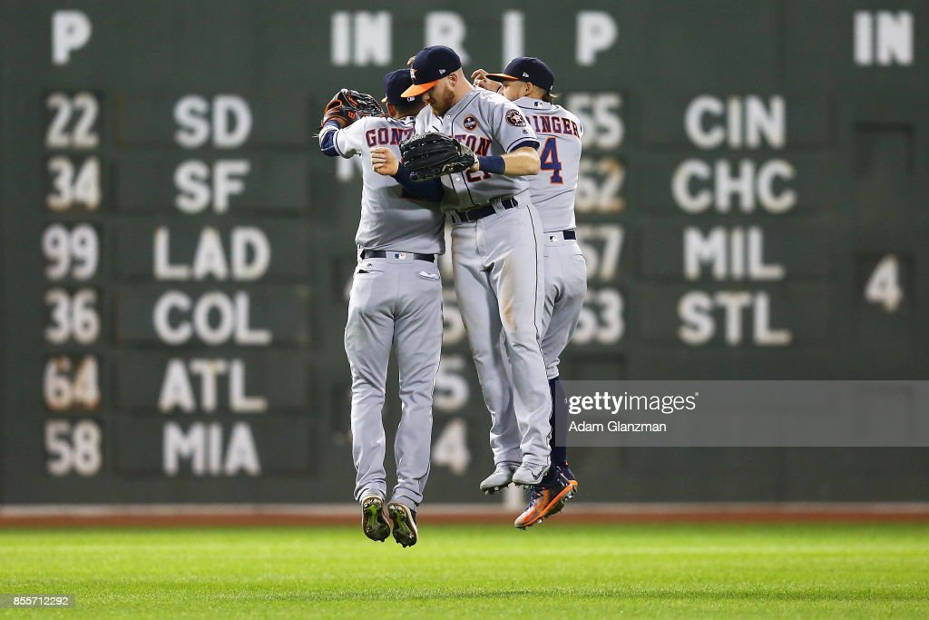 George Springer #4, Marwin Gonzalez #9 and Derek Fisher #21 of the Houston Astros celebrate after a victory over the Boston Red Sox at Fenway Park on September 29, 2017 in Boston, Massachusetts.