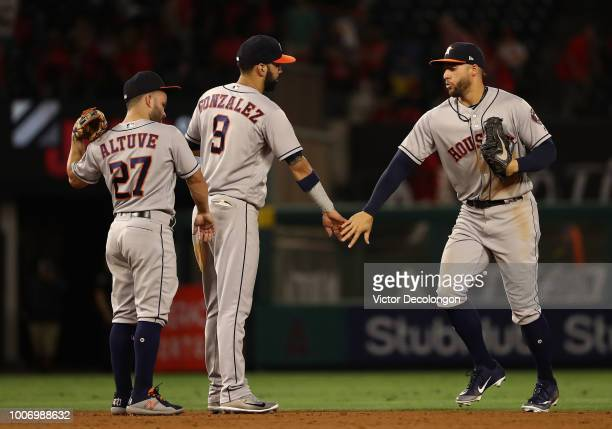 George Springer of the Houston Astros celebrate with teammates Marwin Gonzalez and Jose Altuve after the MLB game against the Los Angeles Angels of...