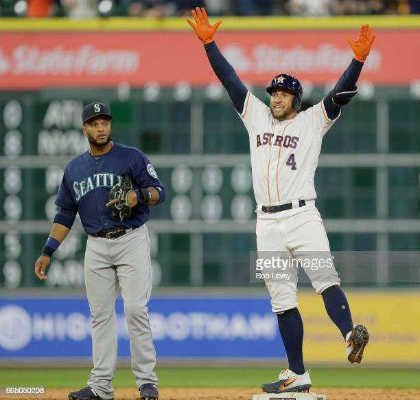 George Springer of the Houston Astros celebrates after hitting a two run double in the seventh inning as Robinson Cano of the Seattle Mariners looks...
