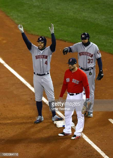 George Springer of the Houston Astros celebrates his twoRBI single with first base coach Alex Cintron as Steve Pearce of the Boston Red Sox reacts in...