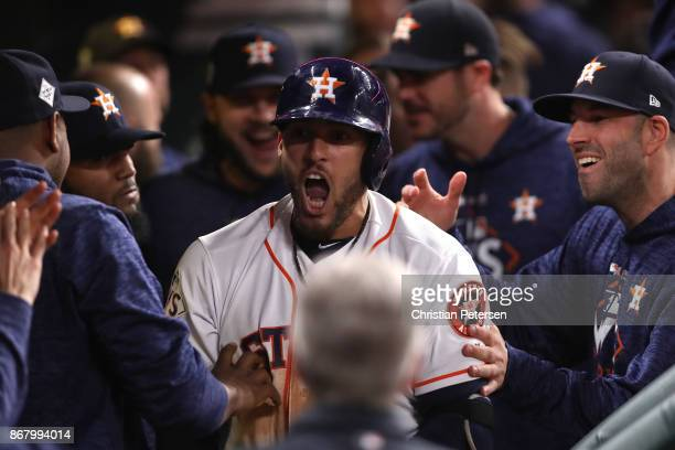 George Springer of the Houston Astros celebrates in the dugout with teammates after a solo home run during the seventh inning against the Los Angeles...
