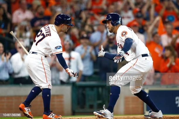 George Springer of the Houston Astros celebrates with Jose Altuve after hitting a solo home run off Corey Kluber of the Cleveland Indians in the...