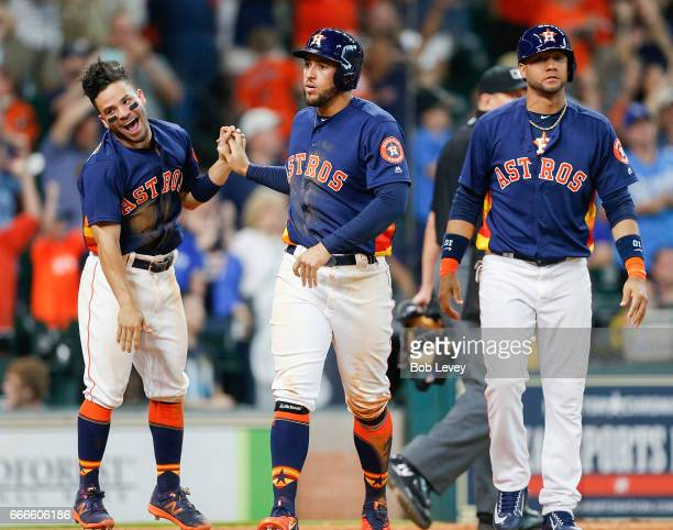 George Springer of the Houston Astros celebrates with Jose Altuve and Yuli Gurriel after scoring on a walk in the second inning against the Kansas...