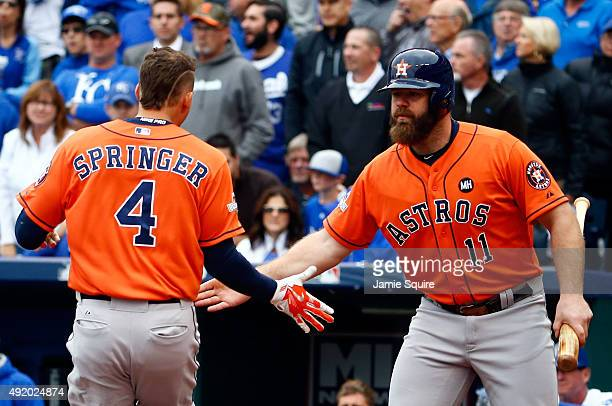 George Springer of the Houston Astros celebrates with teammate Evan Gattis after scoring a run off of a double hit by Colby Rasmus in the first...