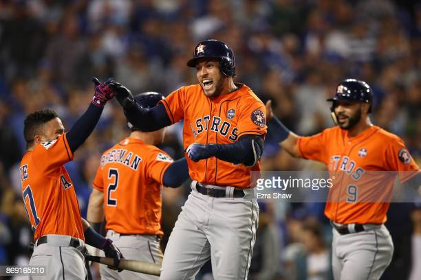 George Springer of the Houston Astros celebrates with teammates after hitting a two-run home run during the second inning against the Los Angeles...