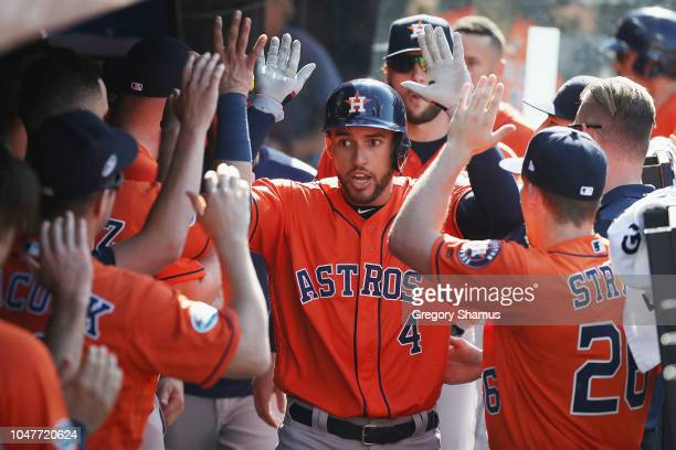 George Springer of the Houston Astros celebrates with teammates in the dugout after hitting a solo home run in the fifth inning against the Cleveland...
